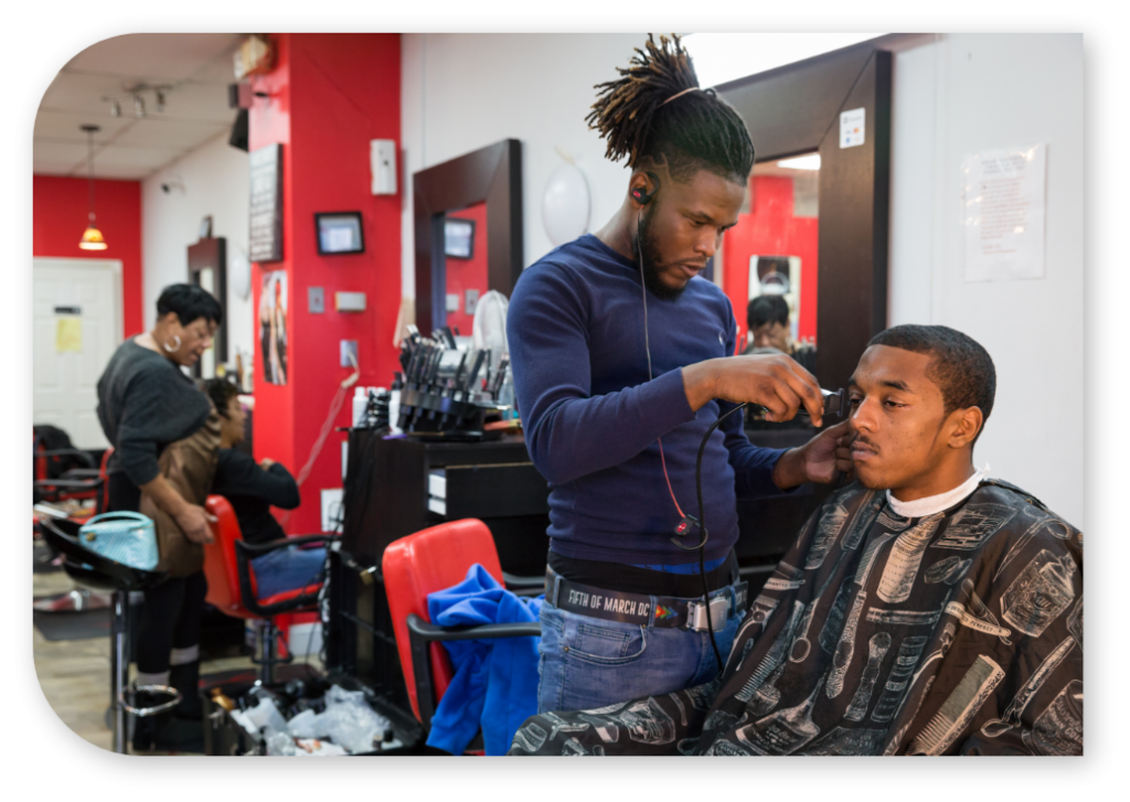 A barber cutting hair in a barbing studio