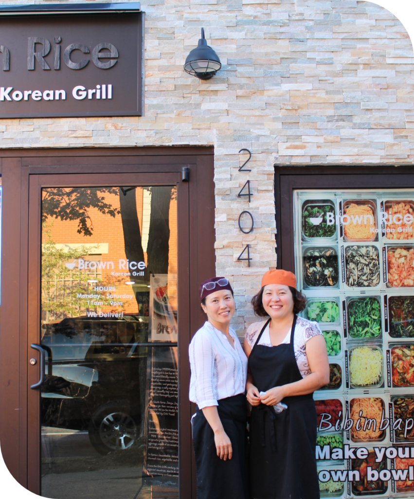 Two ladies standing in-front of their restaurant Brown Rice